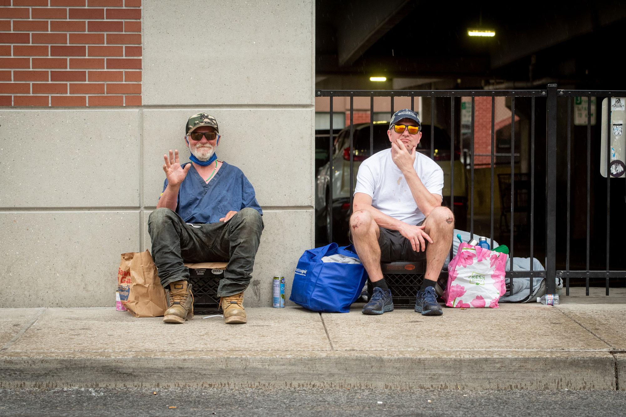 two men sitting on sidewalk